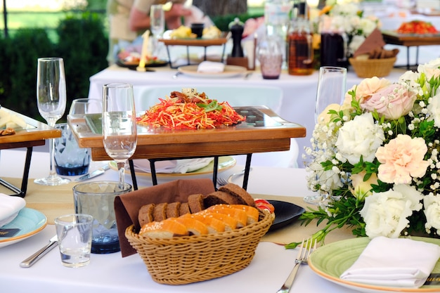 Fresh salad on a wooden plate on a banquet table decorated with elegant floral bouquet. Premium Photo