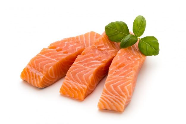 Свежее филе лосося с базиликом на белом фоне. Premium Фотографии