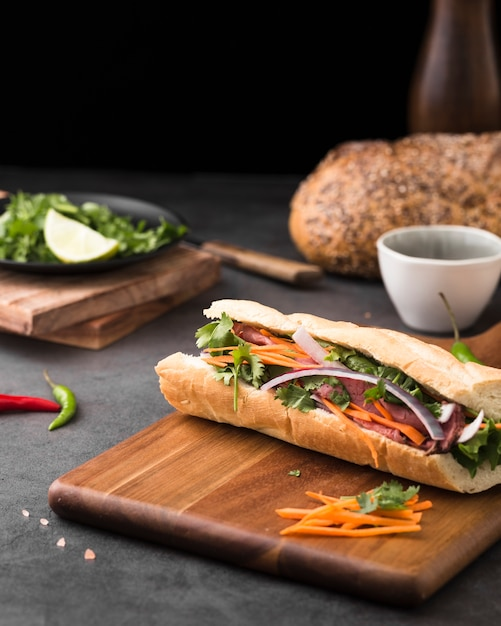 Fresh sandwich on chopping board with carrots Free Photo