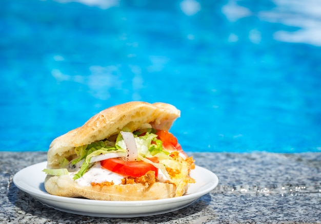 Fresh sandwich on a plate near the swimming pool Premium Photo