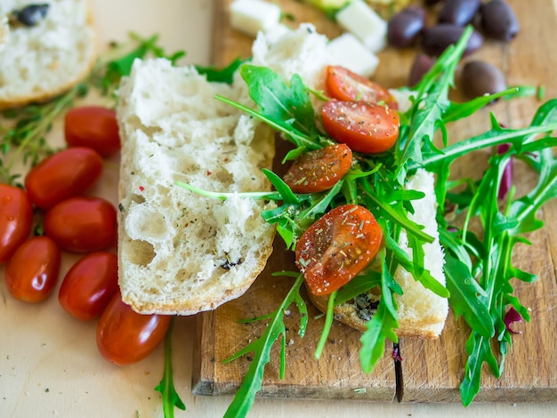Fresh sandwich with cherry-tomatoes, goat cheese, olives and arugula on a wooden kithchen board Premium Photo
