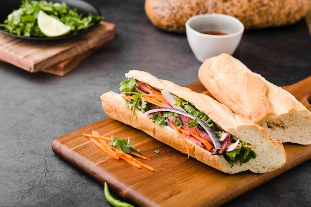 Fresh sandwiches on chopping board with sauce Free Photo