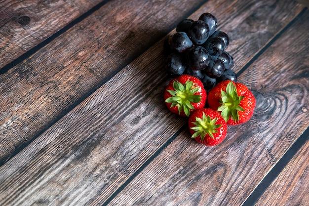 スコットランドの新鮮なイチゴと木製のテーブルの上に黒ブドウ 無料写真