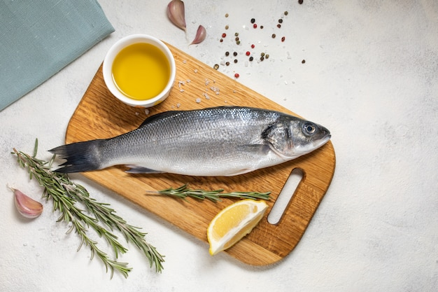 Fresh sea bass fish and ingredients for cooking, lemon and rosemary. white background top view. Premium Photo