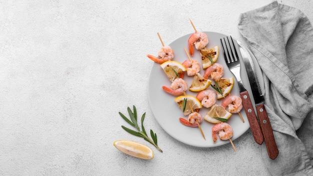 新鮮な魚介類のエビの串焼きとカトラリー 無料写真