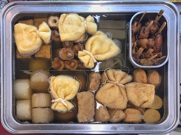 Fresh several japanese boiling oden on hot soup tray. Premium Photo