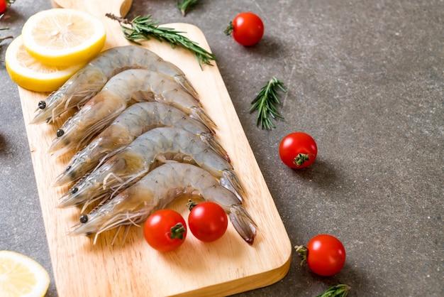 Fresh shrimps or prawns raw on wooden board Premium Photo