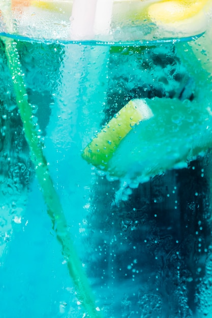Fresh slice of lemon floating in blue cold cocktail with bubbles Free Photo
