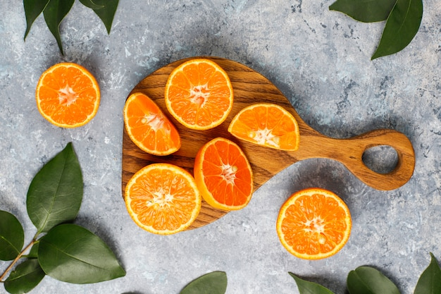 Fresh sliced oranges on cutting board on concrete surface Free Photo