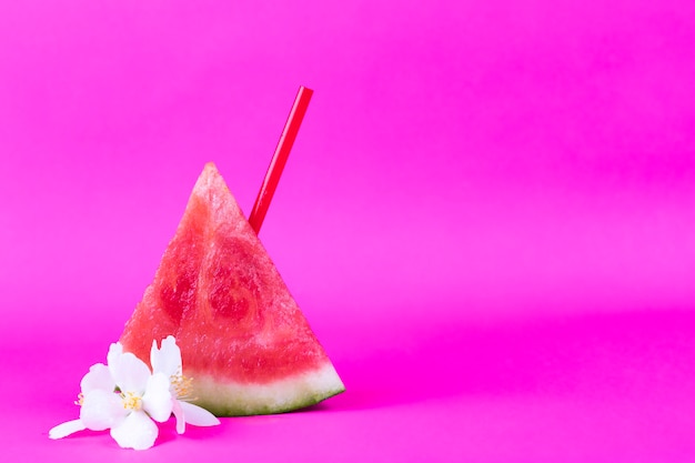 Fresh sliced water melon with pipe and white exotic flowers on a bright pink background Premium Photo