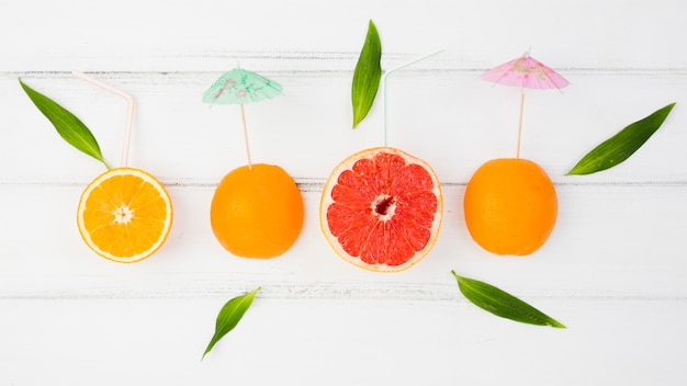 Fresh slices of citruses with decorative umbrellas and green leaves Free Photo