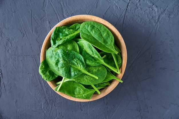 Свежие листья шпината в деревянной миске на темном фоне. органическая еда Premium Фотографии