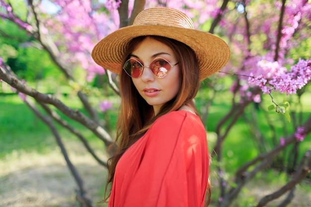 Ritratto di primavera fresca di donna sorridente carina in abito elegante corallo, in cappello di paglia che gode della giornata di sole Foto Gratuite