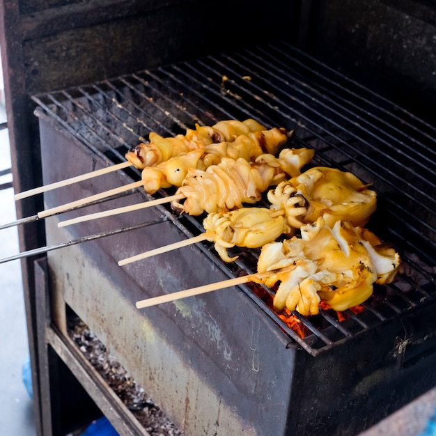 Fresh squid barbeque grilled on charcoal stove Premium Photo