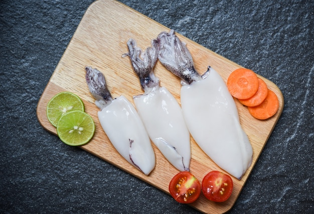 Fresh squid on wooden cutting board top view Premium Photo