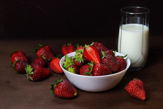 Fresh strawberries in ceramic bowl and a glass of milk  on dark wooden background Premium Photo