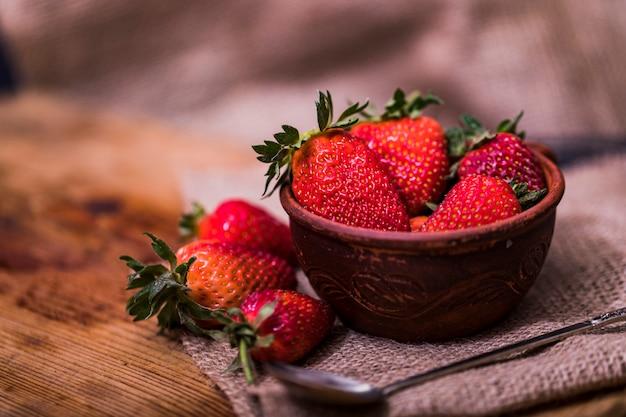 低キーシーンで木製のテーブルの上にボウルに、新鮮なイチゴ。 Premium写真