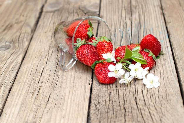 木製のテーブルのガラスのコップに新鮮なイチゴ Premium写真