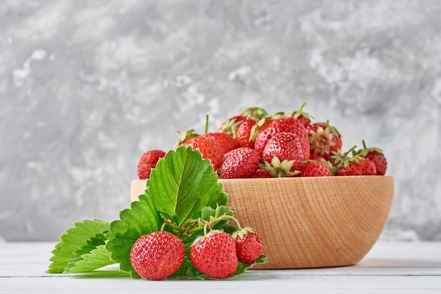 Fresh strawberries in a wooden bowl and green leaves on gray Premium Photo