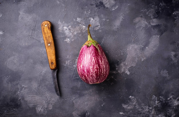 Fresh striped purple aubergines on grey background Premium Photo