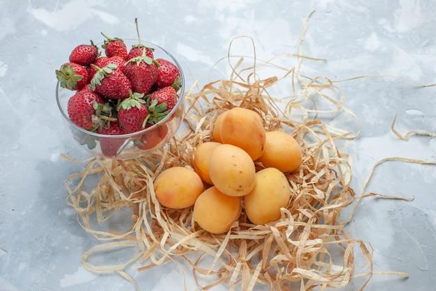 新鮮な甘いアプリコットは白地に赤いイチゴとまろやかな果物 無料写真