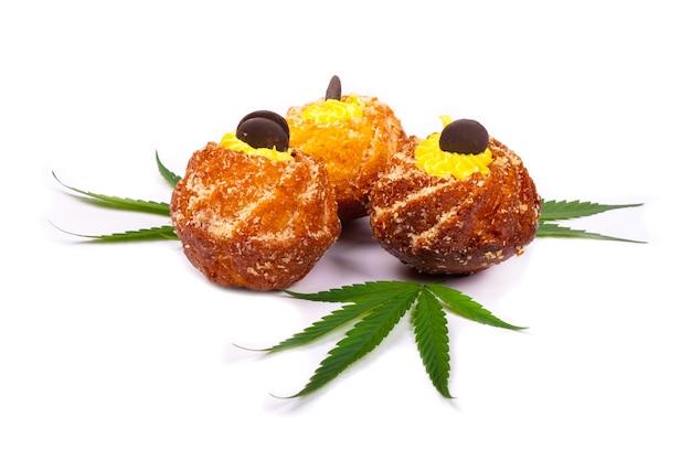 マリファナと新鮮な甘い焼き菓子、大麻植物と3つのカップケーキの葉に孤立した白い背景、お菓子、デザート。 Premium写真