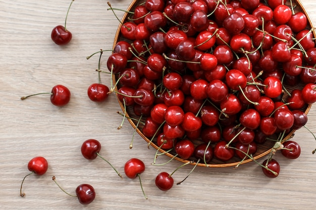 Fresh sweet cherry on a wooden plate on a table. Premium Photo