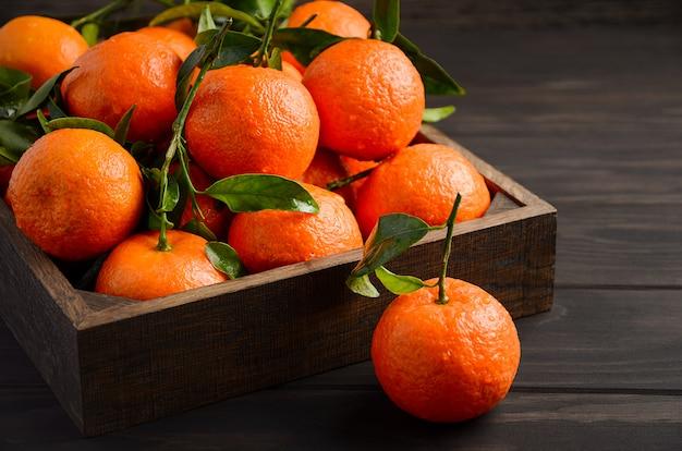 Fresh tangerine clementines with leaves on dark wooden background. Premium Photo