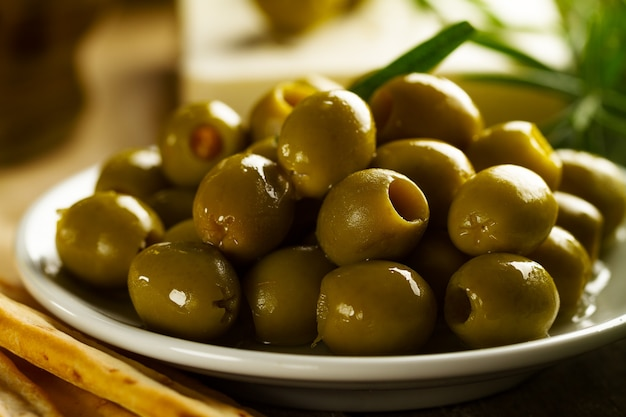 Fresh tasty greek green olives with grissini and fresh rosemar<. closeup. mediterranean food.