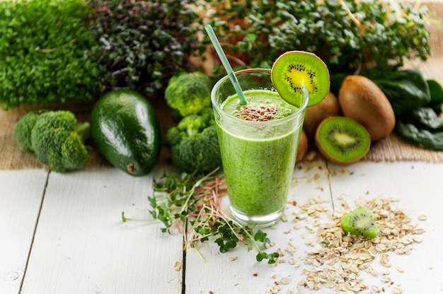 Fresh and tasty green smoothie with ingredients on wooden surface Premium Photo