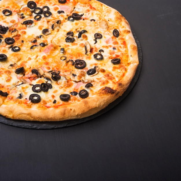 Fresh tasty pizza with olives and meat topping on slate over dark backdrop Free Photo