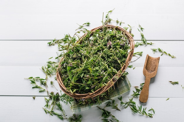 Fresh thyme in a basket on a wooden table Premium Photo