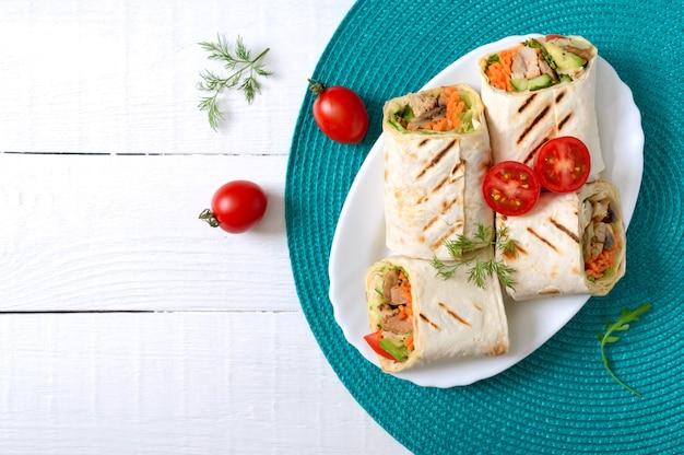 Свежие тортилья обертывания с курицей, грибами и свежими овощами. курица мексиканская буррито. вкусная закуска. блюда из лаваша. концепция здорового питания Premium Фотографии