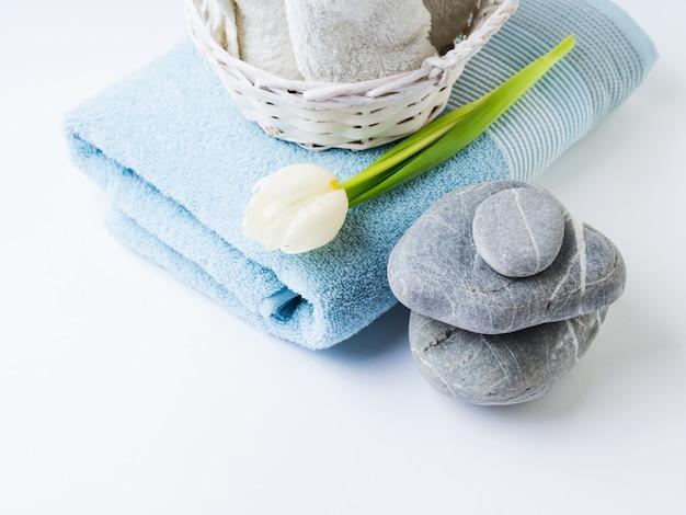 Fresh towels and stones on white background Premium Photo