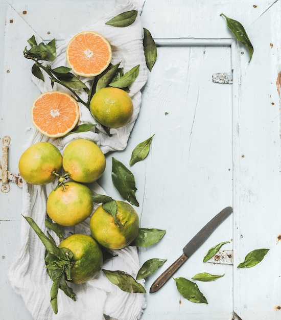 Fresh turkish tangerines with leaves over blue rustic wooden backdrop, top view Premium Photo