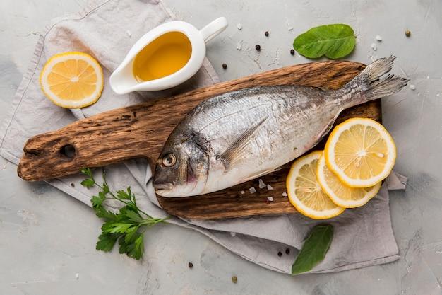レモンスライスと木の板上の新鮮な未調理の魚 Premium写真
