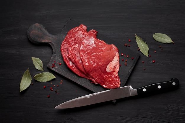 ナイフで木の板に新鮮な生肉 無料写真
