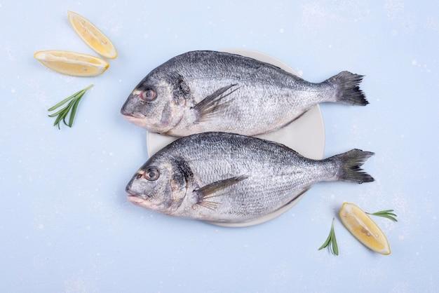 Pesce di mare crudo fresco e fette di limone Foto Gratuite