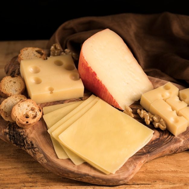 Fresh variety of cheeses with walnut and bread on wooden textured tray Free Photo