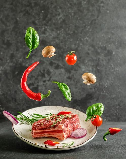 Свежий стейк из телячьей кости на тарелке с летающими ингредиентами для приготовления на темном фоне Premium Фотографии