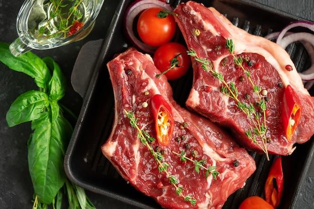 Свежие стейки из телячьей кости на сковороде для гриля со специями и зеленью Premium Фотографии