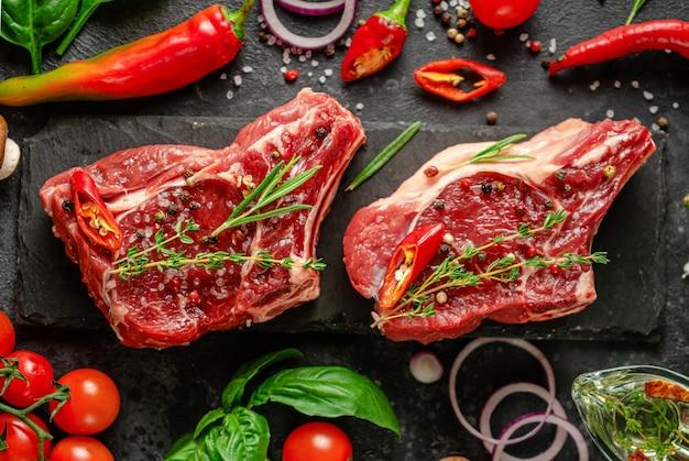 Свежие стейки из телячьей кости со специями, овощами и зеленью на темном фоне. плоская планировка, крупный план. Premium Фотографии
