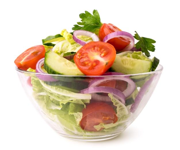 Салат из свежих овощей в стеклянной тарелке на белом, крупным планом. Premium Фотографии