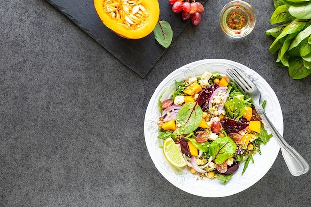 ビートルート、ルッコラ、赤玉ねぎ、スイバ、ひよこ豆、カボチャ、ブドウの新鮮な野菜サラダを黒いテーブルの白いプレートに。上面図 無料写真
