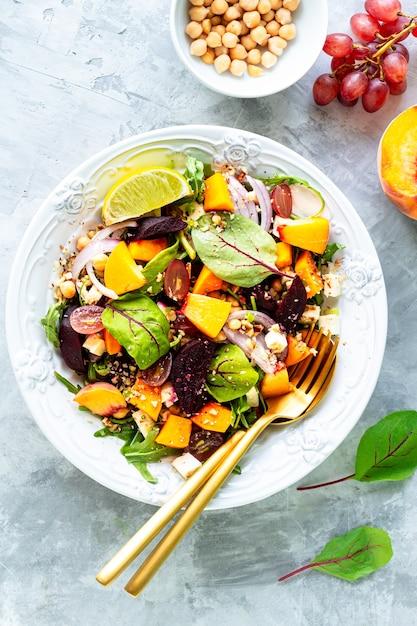 白い石の上の白いプレートにビート、ルッコラ、赤玉ねぎ、スイバ、ひよこ豆、桃、ブドウの新鮮な野菜サラダ。上面図 無料写真