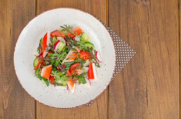 Fresh vegetable salad with crab sticks. Premium Photo