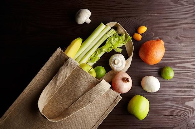 Свежие овощи и фрукты в многоразовой хозяйственной сумке на деревянном столе Premium Фотографии