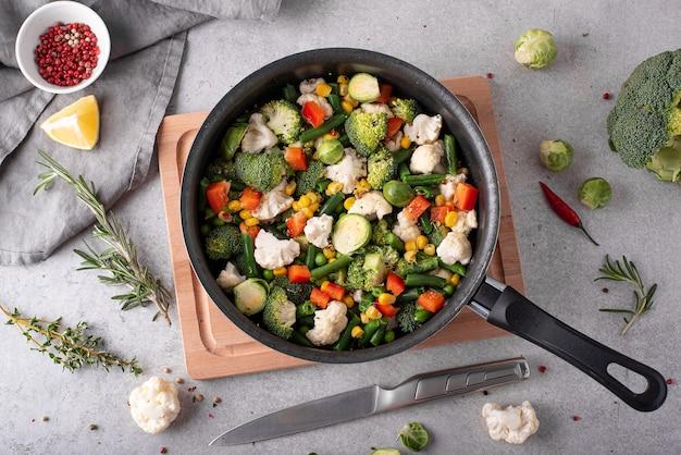 Fresh vegetables - broccoli, green beans, peas, cauliflower stewed in a saucepan, top view Premium Photo