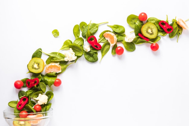 Fresh vegetables and fruits arranged in curved shaped on white backdrop Free Photo