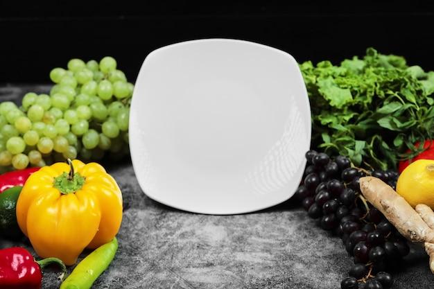 新鮮な野菜、ブドウ、ピーマン、緑、レモン、トマト、暗い背景の白いプレート。 無料写真